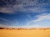 Weisse Wolken, blauer Himmel und gelber Wüstensand